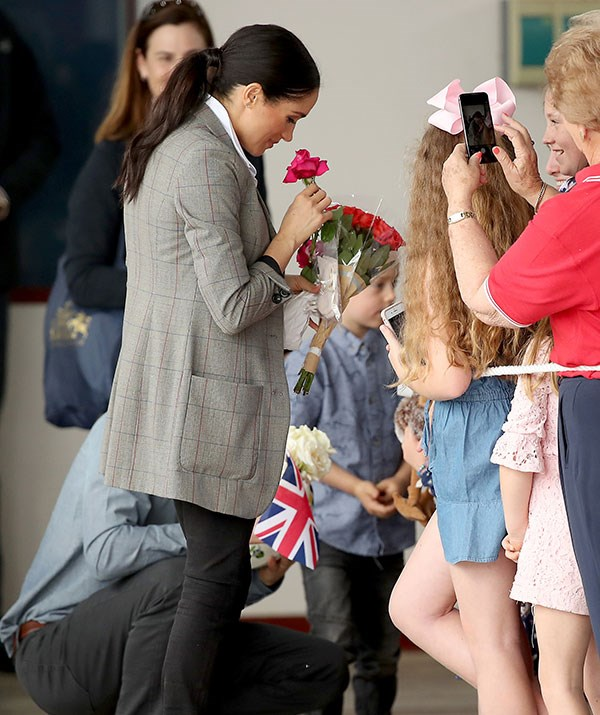 Meghan stops to smell the roses, quite literally.