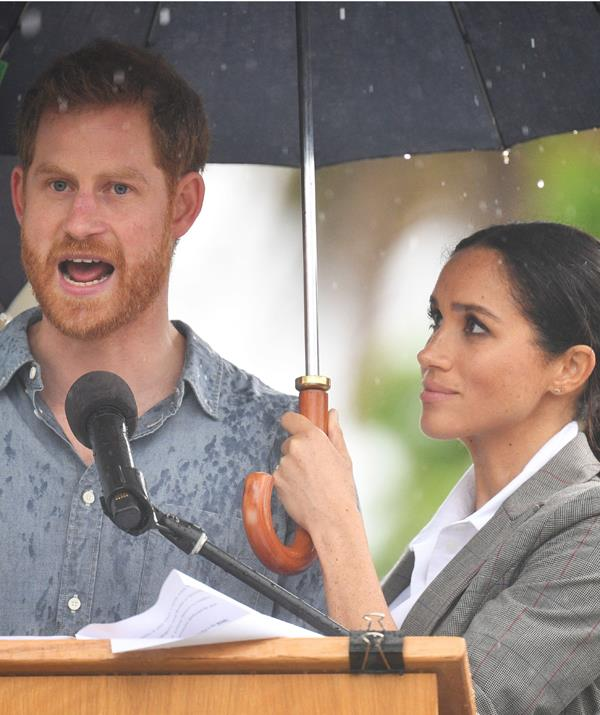 Super Megs held the umbrella for Prince Harry as he made his speech in the downpour. *(Image: Rex)*