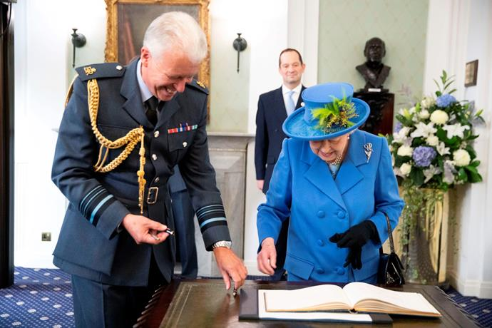 The gloves came off as she signed the visitors book. *(Image: Getty Images)*