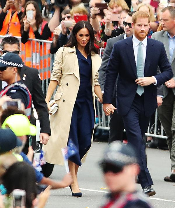 Hello Melbourne! The royals landed in the garden city on Thursday morning, with Meghan wearing a deep navy blue dress by Australian designer Dion Lee paired with the same Martin Grant trench coat she wore in Sydney two days ago. We love a recycled look! *(Image: Getty Images)*