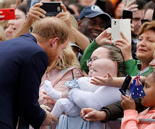 Showing off his paternal side, Prince Harry coos at a baby on day three of the royal tour.