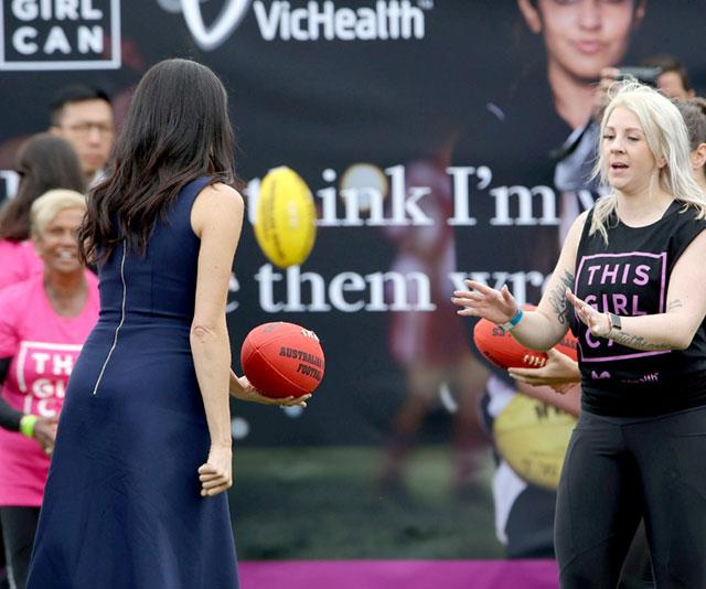 She's a natural! Meghan tries her hand at AFL. *(Image: @DelMody twitter)*