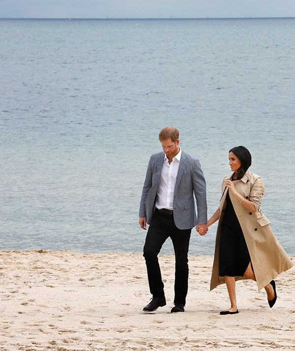 The Duchess made a quick outfit change ahead of their visit to the beach. She wore a black Club Monaco dress paired with her tour-favourite camel trench coat by Martin Grant - and a pair of flats. *(Image: Getty Images)*