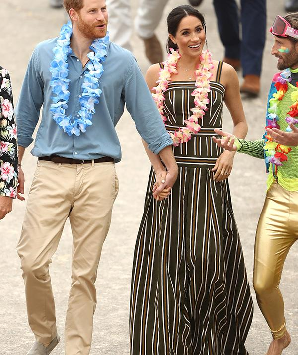 First they nailed country chic, then they won at beach chic! Meghan wore a striped Martin Grant maxi dress to Bondi Beach on Friday - complete with a colourful lei! *(Image: Getty Images)*
