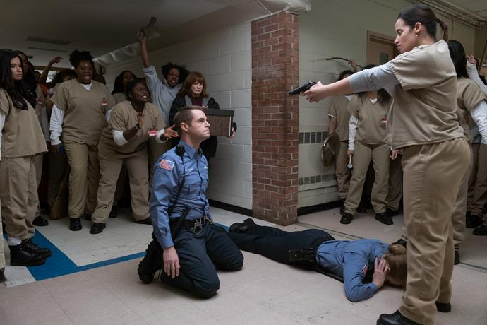 **DAYA AND THE GUN**  When a prison riot breaks out after Poussey's death, CO Humphrey's gun finds itself in the hands of Daya after sliding out of his reach. We're left in an intense cliff-hanger standoff, which leaves Daya pointing the guns at the guards and her fellow inmates cheering her on.