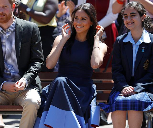 Meghan had a costume change following her visit to Bondi Beach on Friday, opting for a navy and light blue dress designed by London-based label Roksanda. The style is called 'Athena Dress'. Meghan paired the look with some nude heels. *(Image: Getty Images)*