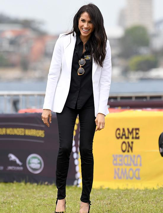 On Saturday afternoon, Meghan and Harry travelled by boat to Cockatoo Island for the Invictus Games Jaguar Land Rover Driving Challenge. The Duchess looked effortlessly chic in a white Altuzarra blazer, an official Invictus Games shirt and black skinny jeans - not to mention those lush locks! *(Image: Getty Images)*
