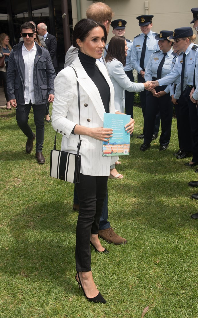 After a late night at the Invictus Games opening ceremony, Duchess Meghan took a well deserved rest on Sunday morning. But she was back in action on Sunday afternoon looking stunning as ever in a L'Agence pinstripe blazer along with a long-sleeved turtleneck and black skinny jeans. *(Image: Getty Images)*