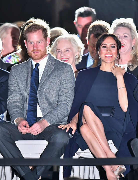 """A wild thunderstorm on Saturday evening didn't faze Meghan as she stepped out for the (slightly delayed) opening ceremony in a navy blue Stella McCartney dress. Stella is one of Meghan's favourite designers - she also created the Duchess's [beautiful high-neck sleeveless halter gown for her post-wedding reception](https://www.nowtolove.com.au/fashion/fashion-news/meghan-markle-second-royal-wedding-dress-48442