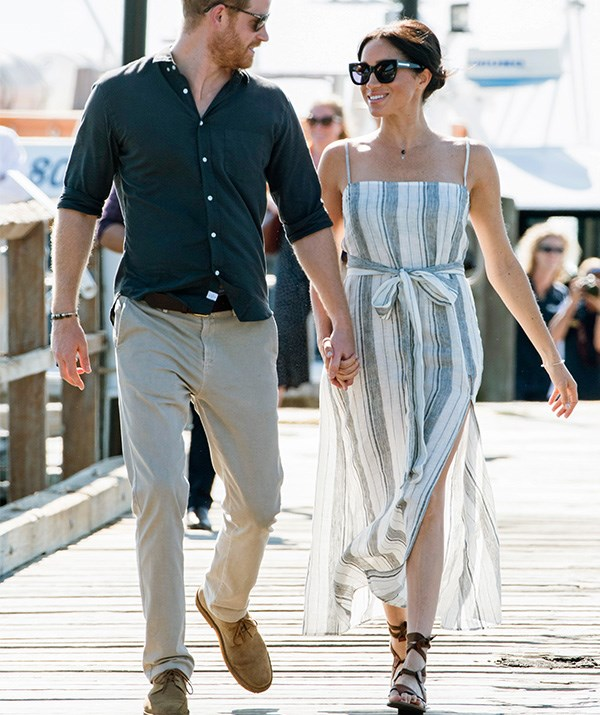 After taking a break from the morning's official engagements, Meghan stepped out in Kingfisher Bay with Prince Harry on Monday afternoon. She looked refreshed and radiant in a Reformation striped maxi-dress with a daring split, along with gladiator sandals. *(Image: Getty Images)*