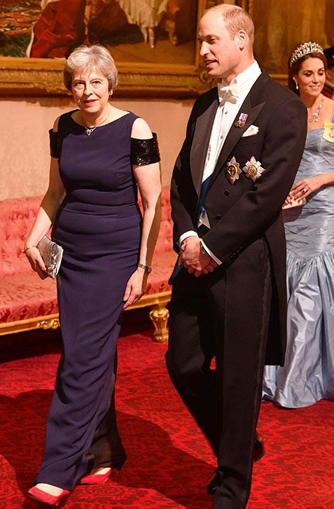 Prince William escorts Prime Minister Theresa May into the banquet. *(Image: AAP)*