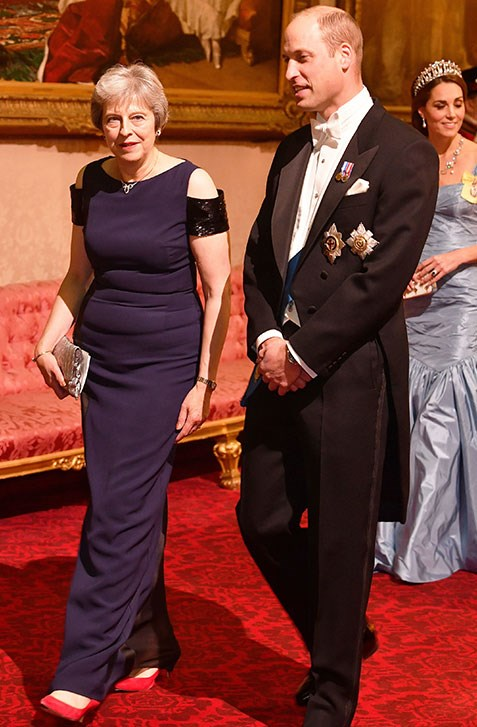Prince William escorts Prime Minister Theresa May into the banquet.