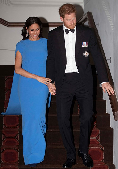 Ending their first day in Fiji on Tuesday, the royal couple stepped out looking classy as ever for an evening Soiree held by the Fijian Prime Minister. Meghan wore a striking blue SAFiYAA 'Ginkgo' cape gown for the event. *(Image: Getty Images)*