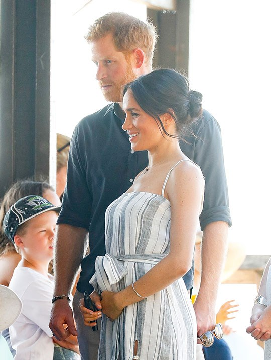 During a walkabout on Fraser Island on Monday, Meghan's loving hand was back on her belly.