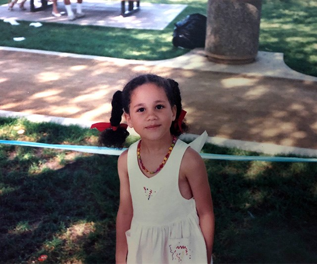 Meghan might be a style icon to the masses now, but she was setting trends even as a young tot. Her rainbow necklace and plaits finished with bow ties in this picture are the image of cute. *(Image: Mega)*