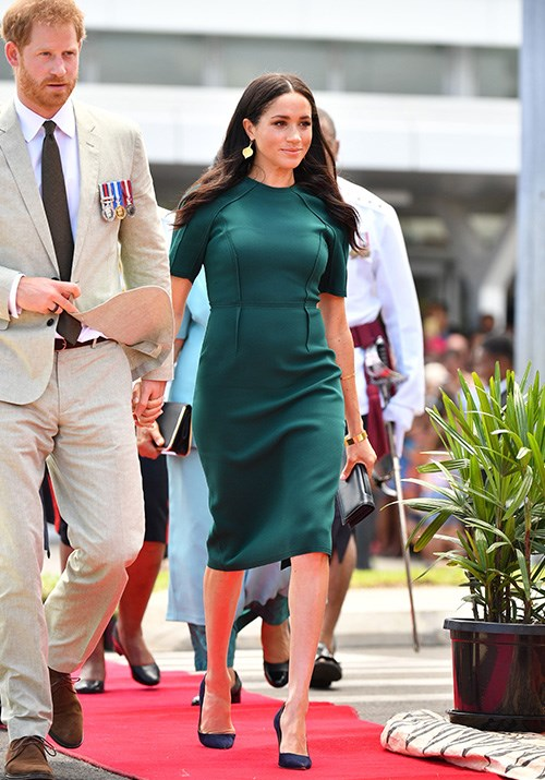 No stranger to a red carpet, Meghan looked effortlessly stunning as she stepped out on her third day in Fiji. The Duchess wore a gorgeous moss green Jason Wu dress as she walked hand-in-hand with husband Prince Harry. *(Image: Rex)*