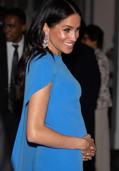 Simply stunning in a blue caped dress by Safiyaa but why no jewels in Meghan's hair? *(Image: Getty Images)*