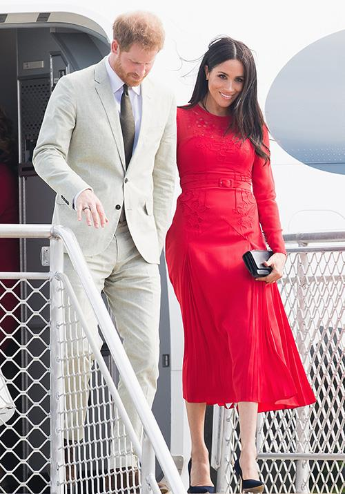 Lady in red alert! Markle looked gorgeous in a bright red Self-Portrait dress as she disembarked from her flight from Fiji to Tonga on Thursday afternoon. *(Image: Getty Images)*