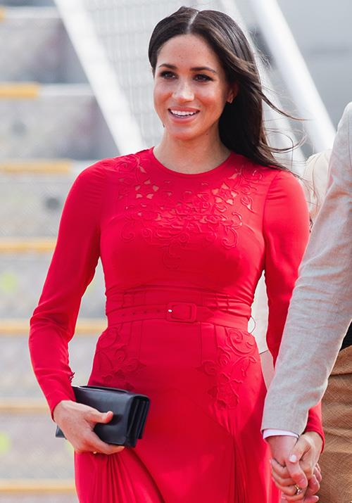 Paired with a black Dior clutch, the ensemble was one of Meghan's most eye-catching looks from the tour. *(Image: Getty Images)*