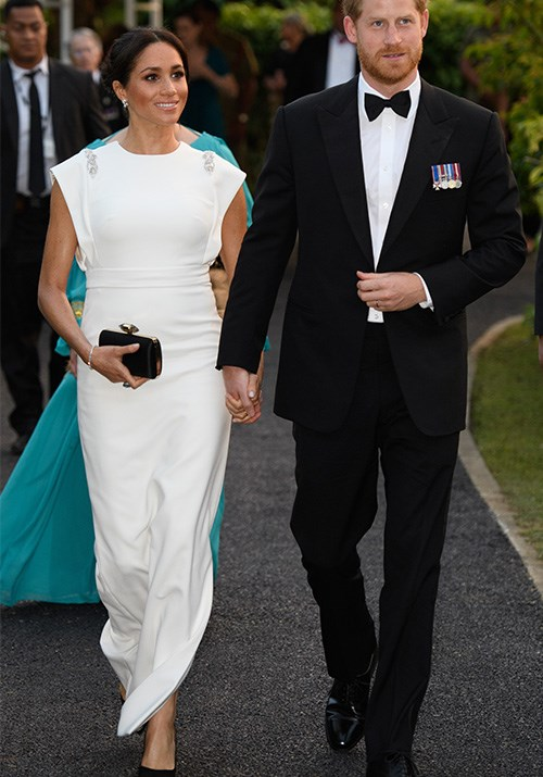 """Stepping out for a private evening soiree in Tonga with King Tupou VI and Queen Nanasipauʻu, Duchess Meghan and Prince Harry were a sight to behold - and we couldn't ignore the [striking resemblance to their wedding day style](https://www.nowtolove.com.au/royals/british-royal-family/meghan-markle-prince-harry-tonga-white-dress-52049