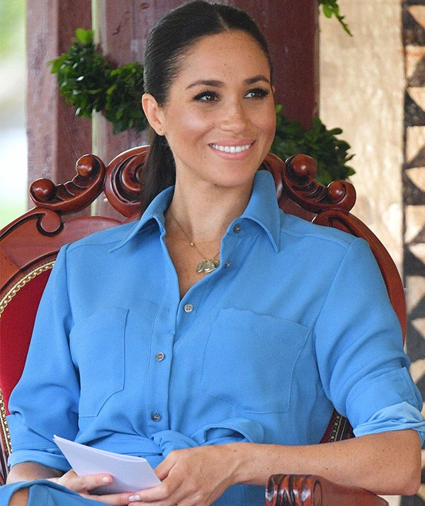 In her second outfit of the day, the Duchess changed into this blue Veronica Beard dress for a visit to Tupou College in Tonga - we're loving this stunning colour on Meghan! *(Image: Rex)*
