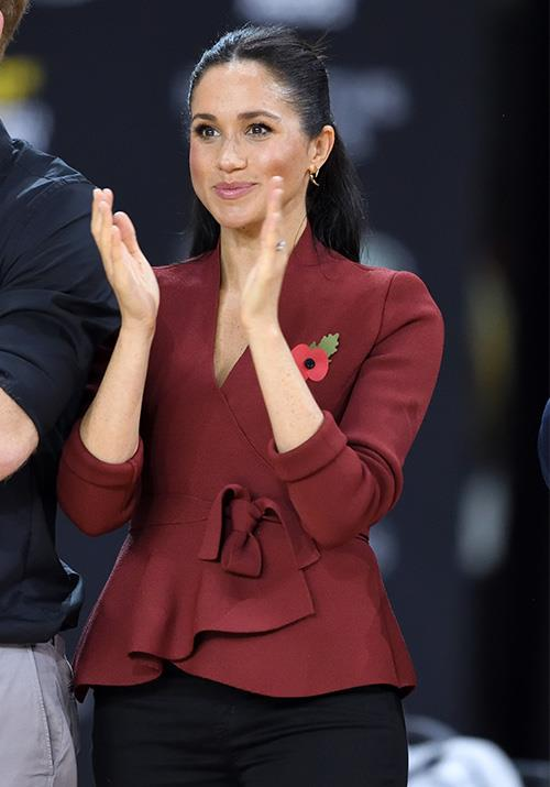 Wearing her hair in a half-up half-down top knot, Meghan was an enthusiastic supporter from the sidelines. *(Image: Getty Images)*