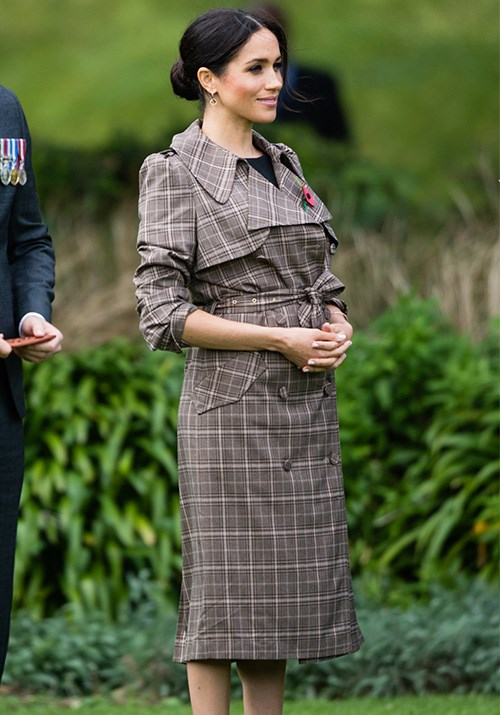 Meghan stepped off the plane in New Zealand looking radiant in a printed trench coat by Kiwi designer Karen Walker. Underneath, the Duchess wore a simple black maternity dress by ASOS. *(Image: Getty Images)*