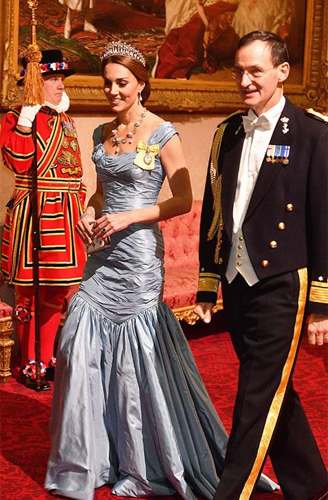 The Duchess of Cambridge walks into the dinner with Rear Admiral Ludger Brummelaar.