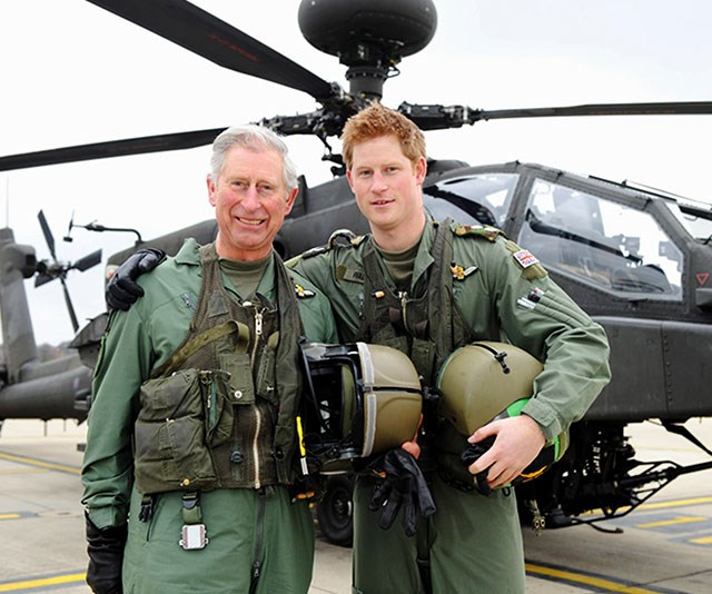 **Moving up the ranks:** A proud Prince Charles poses with Prince Harry following his son's promotion to captain of an Apache Helicopter in 2011. *(Image: Getty)*