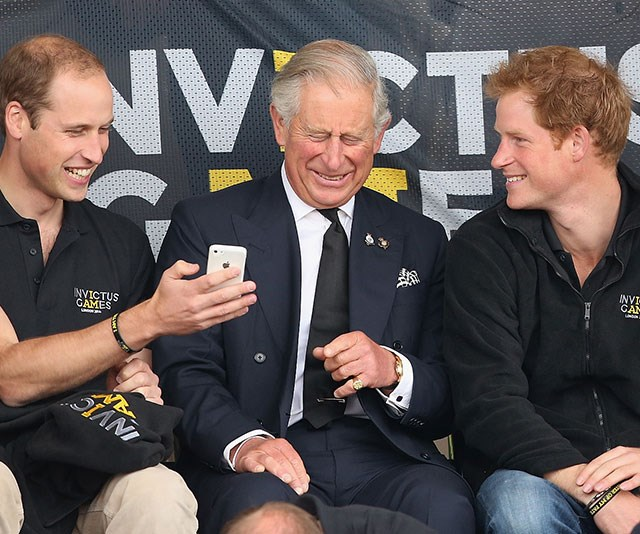**Royal flush:** We'd love to know what's on that phone! The boys have their dad in a fit of giggles at the 2014 Invictus Games in London. *(Image: Getty)*