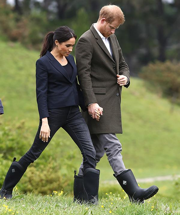 Continuing their wet-weather wardrobe streak, the royals embraced woodland chic by donning gumboots as they walked through the Queen's Commonwealth Canopy in Auckland, NZ. Meghan wore a Karen Walker blazer and J Crew jeans for the occasion. *(Image: Getty Images)*