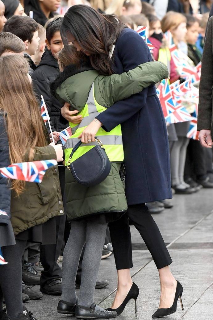 Duchess Meghan shows what a natural mum she's going to be with this embrace of another lucky schoolgirl on the same royal visit to Birmingham with Prince Harry. *(Image: Getty Images)*