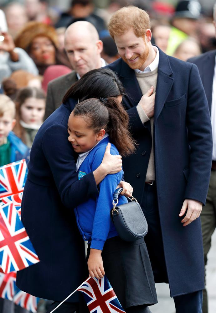 In keeping with Meghan's girl power passions, the Duchess was snapped hugging a schoolgirl in Birmingham on International Women's Day back in March. *(Image: Getty Images)*