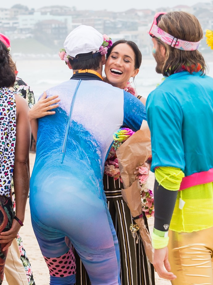 The laughing Duchess Meghan threw her weight – and her smiling cuddles – behind the surfing mental health initiative OneWave on Sydney's Bondi Beach. *(Image: Getty Images)*