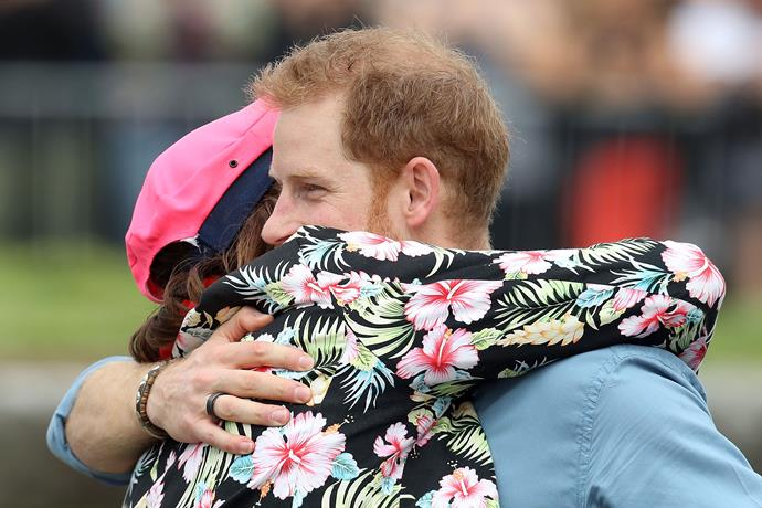 Man hug! The prince wasn't going to shy away from getting up close and personal with one of the OneWave team, even if they were dressed in startling fluro surf gear. *(Image: Getty Images)*