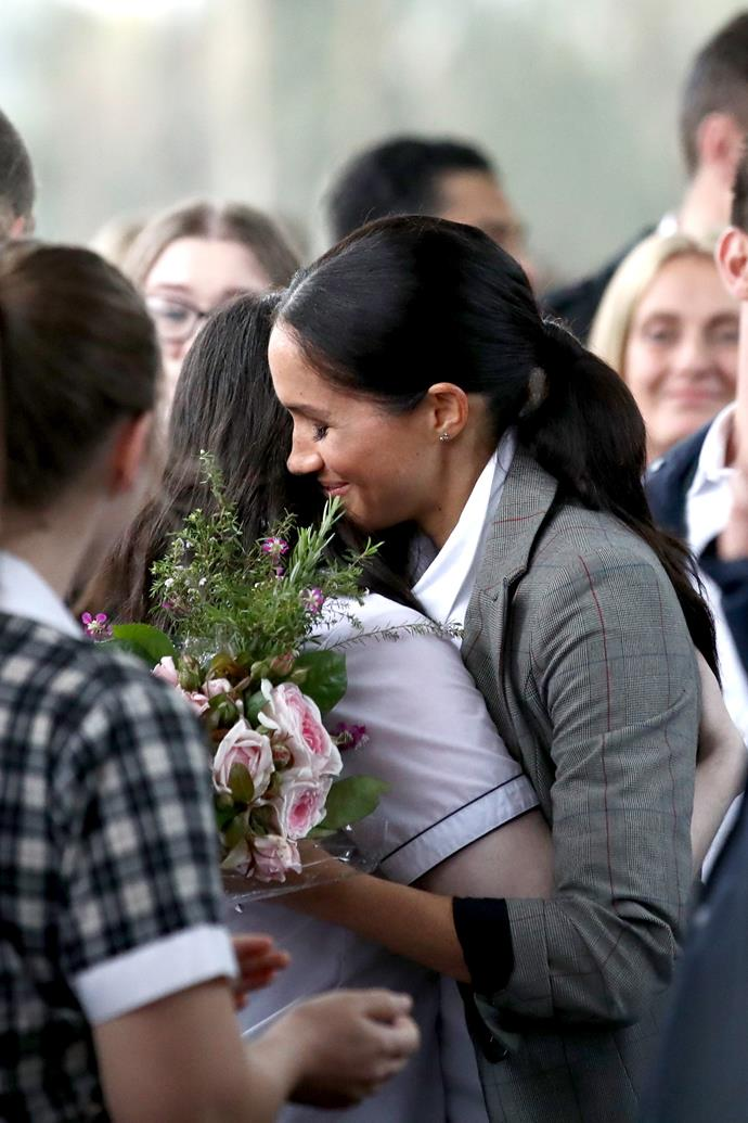 The Duchess gave a warm hug to one lucky student at Dubbo College during the Royal Tour of Australia and the South Pacific. The newly-pregnant royal was mobbed by crowds wherever she went but made sure to give as much personal attention to as many fans as she could. *(Image: Getty Images)*