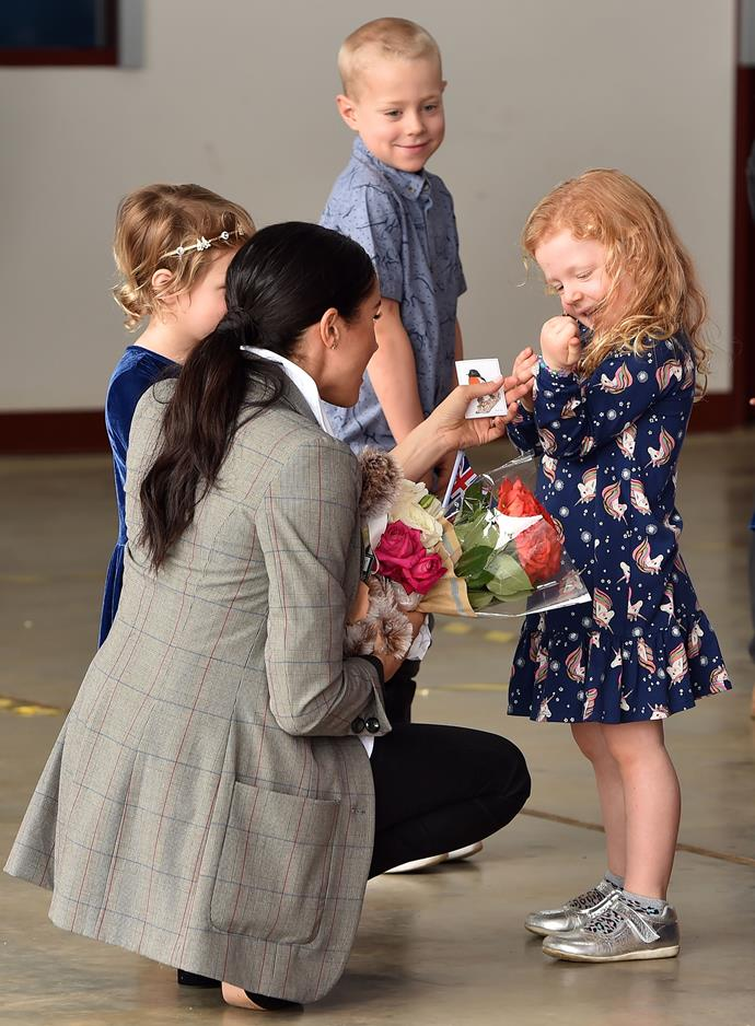 Duchess Meghan crouched down earlier in the day to pacify three-year-old Keiley Storer who had reluctantly given up her posy of gerberas and daisies to the royal visitor. And yes, warm-hearted Meghan knew instinctively that Keiley's smile would be restored if she gave one of the flowers back!  *(Image: Getty Images)*