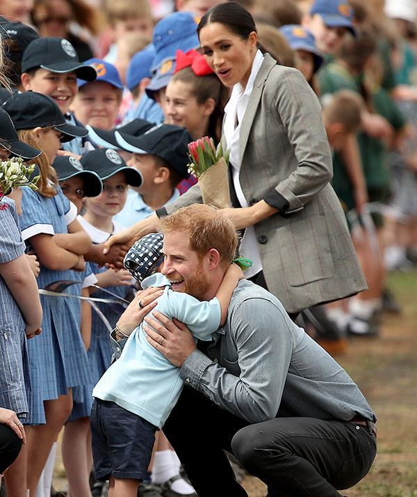 Prince Harry couldn't miss out on the cuddle action when it came to five-year-old Luke Vincent from Buninyong School. The youngster seemed fascinated by Harry's ginger beard! *(Image: Getty Images)*