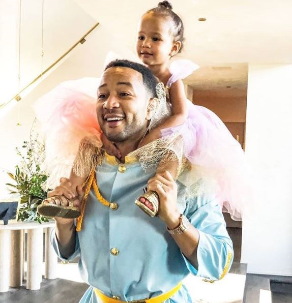 John Legend dressed as Prince Charming as little Luna, his two-year-old daughter, played a princess on his shoulders!