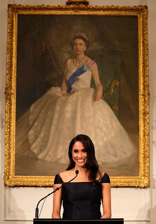 The Duchess fittingly delivered her speech beneath a striking portrait of Queen Elizabeth II. *(Image: Getty)*