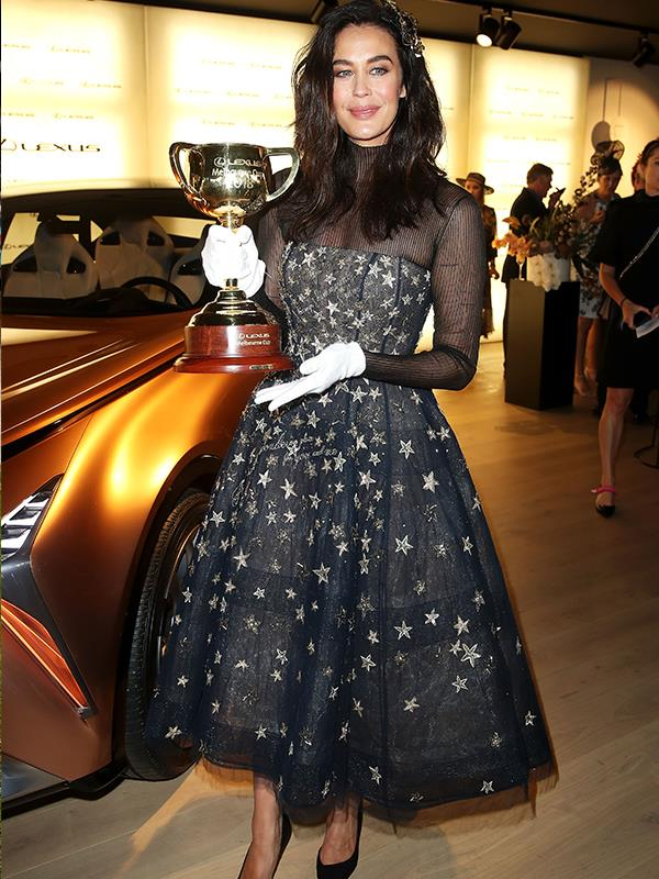 Megan Gale is oozing classic chicness as she holds the coveted Melbourne Cup. *(Image: Getty Images)*