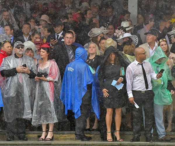 The crowds looked a little damp as they huddled for cover. *(Image: Getty Images)*