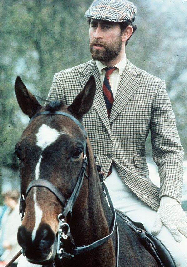 It's a little known fact but Charles sported a smart naval beard in the 70s. Here, the royal rides horseback dressed in traditional tweeds. *(Image: Getty)*