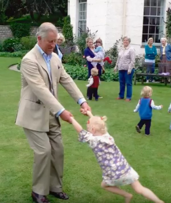 The Prince playing with little Lola Parker Bowles, granddaughter of Camilla, Duchess of Cornwall. *(Image: BBC/Clarence House)*