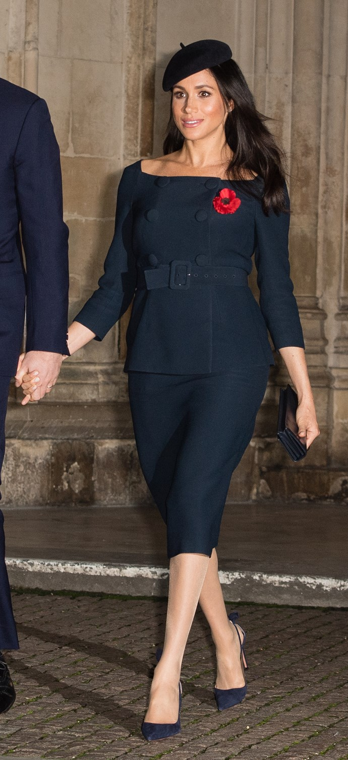 Ever the fan of a boat neck-style neckline, Meghan wore a striking navy blue ensemble for an event on Remembrance Day. Her hat and heels matched perfectly with her top and skirt combo. *(Image: Getty Images)*