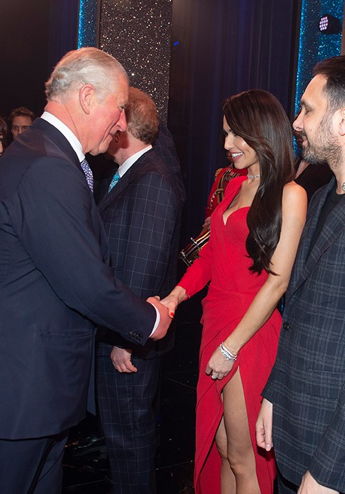 UK popstar Cheryl was ravishing in red as she shook hands with Charles. *(Image: AAP)*
