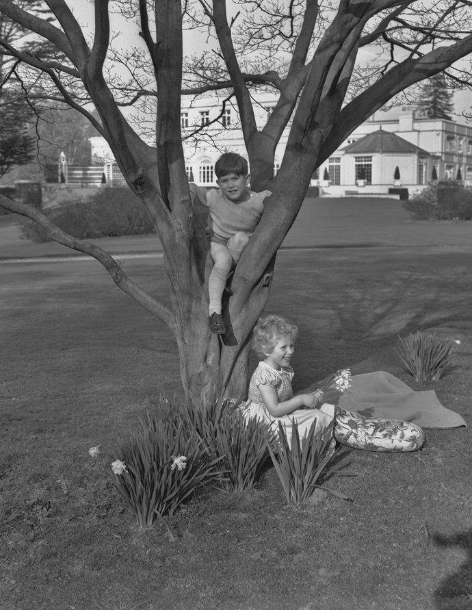 Prince Charles and Princess Anne playing in the garden at the Royal Lodge in Windsor in April 1954. *(Image: Getty)*