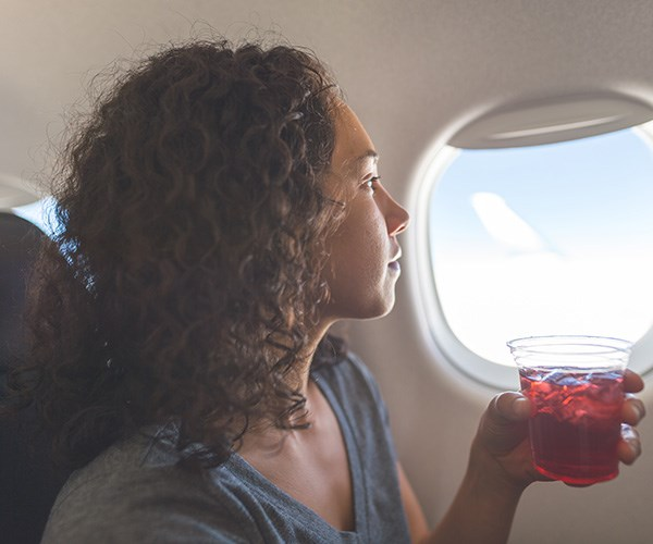 You lose more than two litres of fluid during a 10-hour flight, so stay hydrated. *(Image: Getty Images)*