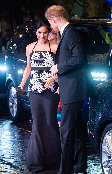 Ever the gentleman, Prince Harry sweetly guided his wife into the venue.