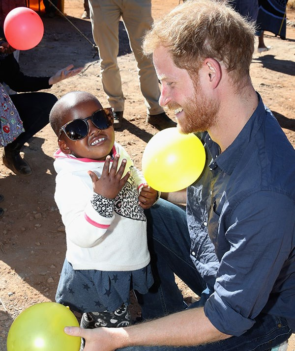 Pictured in June this year on a secret mission to Lesotho, Prince Harry plays with a young child. *(All images: Getty Images)*